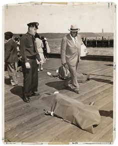 Police officer and lodge member looking at blanket-covered body of woman trampled to death in excursion-ship stampede, New York, August 18, 1941. © Weegee/International Center of Photography