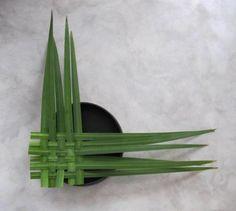 Bloemschikken: een mat weven met bladeren van gele lis en opvullen met Anthurium - Typha bladeren weven