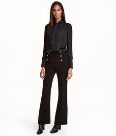 Svart. Ett par byxor i vävd kvalitet med utsvängda ben. Byxorna har hög midja och dekorativ knäppning med knappar fram. Sidfickor och fuskfickor bak. Dold