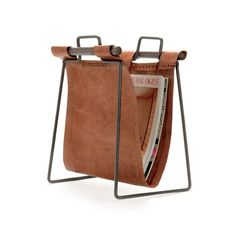 Handsome, rustic, and justa bit of trendiness,the Clint Leather Magazine Standis a perfect accessory for your place. Leather, wood, and iron mix for an industrial yetruggedstand to hold all of your magazines, files, or other reading materials.Dimensions: 13
