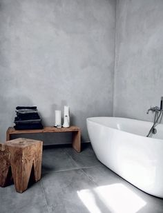 Wit bad in een grijze kamer, met mooie grijze betonnen muren   A white bathtub with grey accents in the room