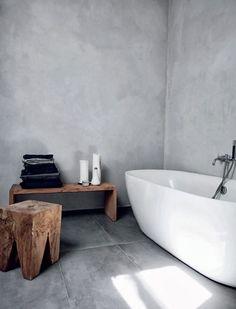 Wit bad in een grijze kamer, met mooie grijze betonnen muren | A white bathtub with grey accents in the room