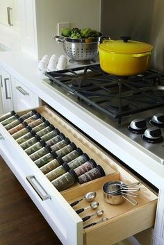 Kitchen with spice rack drawer below gas cooktop. Well organized pull-out spice drawer. Efficient!