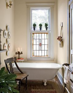 """Downstairs Bathroom:   Every morning, Billy takes his coffee in his """"sanctuary"""" -- the downstairs bathroom. The extra-long bathtub is original to the house; the plates mounted above it are from Billy's grandmother. The stained glass window came from the couple's previous home in Dallas. It provides both privacy and a dash of color. Billy Reid Designer"""
