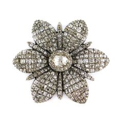 18th century diamond six petal flowerhead brooch, c.1770, centred by an oval rose cut diamond cluster, to slightly curved petals of pointed drop outline, pave set with lines of cushion cut diamonds, diamond line spurs between, close set in silver