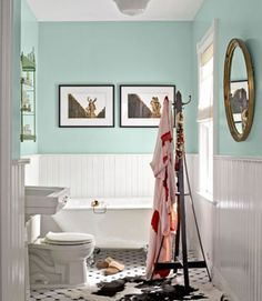 A claw-foot tub from Baths from the Past now offers a view. The room's dark wainscoting got a fresh makeover with white paint, while a coat of Tiffany blue livens up the top half of the walls. Angled tile replaced the outdated linoleum floor.