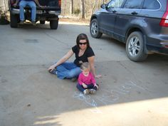 Drawing on the sidewalk with chalk. Momma helping.