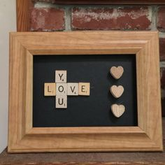 Scrabble tile and wooden hearts decor item in wood frame measuring 8 X 10 outside of frame and 5 X 7 inside frame. Scrabble tiles say Love You in crossword style with three wooden hearts along side. Pieces are glued securely on black background. Would be a great gift for Valentines Day or any other occasion for someone dear to you. There is a hanger on the back for wall hanging.