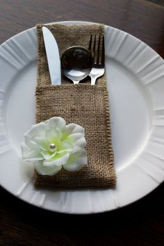 Cutlery holders are made of burlap and decorated with fabric flower finished off with faux pearl..