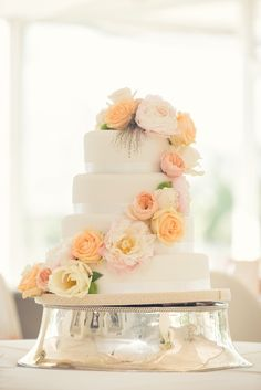 white wedding cake with florals cascading down the side http://www.weddingchicks.com/2014/03/04/garden-wedding-in-peach-and-pink/