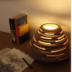 Lámpara de cartón corrugado en forma cónica, con aperturas que generar una celosía lumínica alrededor de la misma. Utilizando el cartón se transforma un material altamente reciclable en un objeto de diseño