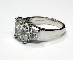 Platinum Three Stone Ring with one 4.50ct. Cushion Cut Diamond and Trapezoid Diamond Side Stones | Three Stone Rings, Signature Collections | Thomas Michaels Designers