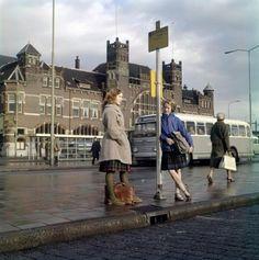 Openbaar vervoer Nederland. Meisjes in plooirok met Schotse ruit en hun schooltassen wachten op de bus voor het spoorwegstation in Haarlem. Zij wachten bij het bushaltebord van buslijn 2 naar Haarlem-Oost. De wachtperrons glimmen van de pas gevallen regen. Op de achtergrond een grijze NZH-bus. Datum onbekend [omstreeks 1965]