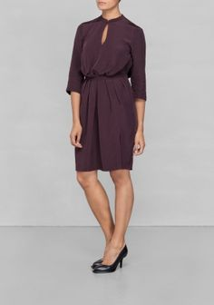 Made from a silky, somewhat shiny, fabric this elegant everyday dress is designed with decorative pleats and a feminine waistband emphasizing the waist.