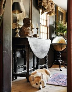 English country cottage style sitting room with a globe and a corgi