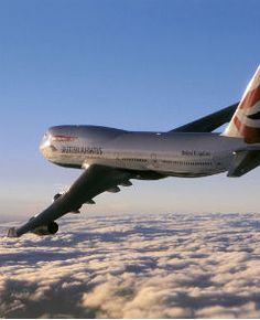 Boeing 747-400 fliegt über bewölktem Himmel.