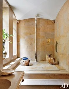 Sun shines into the roomy shower area in fashion designer Stefano Pilati's Paris duplex. The shower fixture was custom made, and the fittings are by Lefroy Brooks | archdigest.com