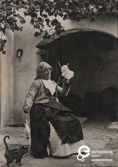 Postcard B/W photo of a woman spinning wool with interested cat - Megara…