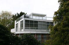 """NEOPLASTICISMO. """"Casa Mees"""". Gerrit Rietveld, 1934-36. La estructura de la casa Mees está formada por pórticos de pilares y vigas de acero, dinteles de hormigón armado en los huecos y paredes de fábrica de ladrillo y hormigón armado en los balcones. Las fachadas están revocadas con una capa plástica tosca de cemento pintada de blanco. Los únicos toques de color son el rojo de la puerta de entrada y el azul de las puertas del garaje."""
