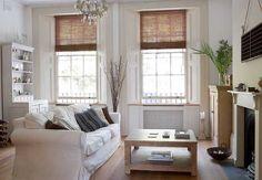 As janelas da sala de estar dão para uma praça de estilo georgiano. Na decoração simples e acolhedora, Mark conseguiu equilibrar as paredes brancas, o piso de madeira carvalho e as cortinas de bambu. O lustre de cristal dá um toque de época