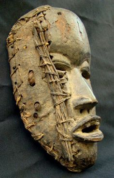 Female mask (Deangle) from the Dan people of Liberia and the Ivory Coast   Wood, pierced for leather and raffia attachments   Early to mid 1900s   These types of masks represent gentle spirits who collect food from the villagers for boys secluded in initiation 'camps'.