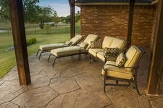Outdoor living area on a stamped concrete patio area under an arbor by Red Valley Landscape & Construction in Norman, OK.