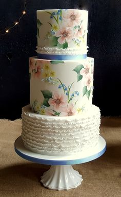 wedding cakes creative Hand painted wedding cake with spring flowers including bluebells, primroses, forget-me-nots and peach anemones. Pretty ruffles and flowers soften the design. Created by Emily Hankins Cakes Small Wedding Cakes, White Wedding Cakes, Wedding Cake Designs, Wedding Cupcakes, Beautiful Cakes, Amazing Cakes, Pretty Cakes, Mini Cakes, Cupcake Cakes