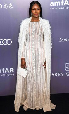 Naomi Campbell is wearing a white beaded Ralph & Russo gown with a long white coat. Glamorous from head to toe! Absolute perfection!