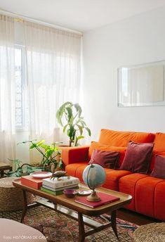f9542bb84a26 Pronta para receber. Sala de estar com sofá laranja tem muitas plantas ...