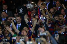 captain Andres Iniesta of FC Barcelona holds the trophy in celebration ahead King Felipe VI of Spain during the Copa del Rey Final match…
