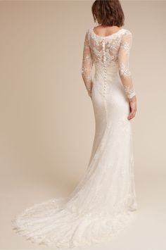 Enveloped in romance, this beautiful long-sleeved bridal gown features ivory floral embroidery and barely-there beading over a soft Chantilly lace layer. Semi-opaque illusion sleeves, row of rear buttons, and elegant train are classic details that are sure to stand the test of time. Designed by Lusan Mandongus. Available in sizes 0 – 14