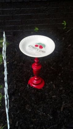 Bird bath made out of an old lamp and a kitchen dish.