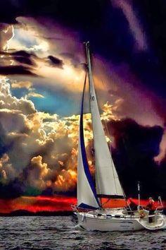 Segelboot mit Farbige Cumuluswolken am Meer