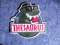 The newest dino in town, Thesaurus, the book munching, synonym spitting dino is a fully embroidered shaped patch measuring 3.75 tall and 3.75 wide.