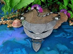 This unique handmade necklace combines a tribal style etched silvertone breastplate with black and clear beads. There are three tiers in the silver