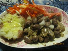 cooked chicken hearts on the plate with buttered baked potato and carrot salad
