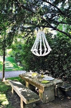 A nice suspended decoration over a stone table in the garden Image via: http://pinterest.com/source/cotemaison.fr