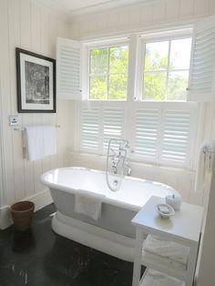 white soaking tub plantation shutters