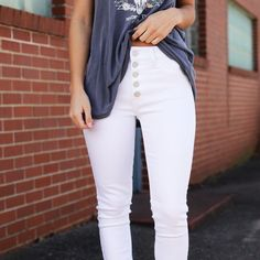 A fun twist on your basic white skinny jean.. these pants feature an exposed button closure and frayed hems! They pair perfectly with basically anything.