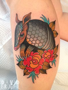 Traditional tattoo of an armadillo and folk art roses on a leg. By David Bruehl at RedLetter1 in Tampa, Florida