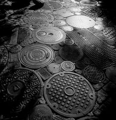 A collection of manhole covers from the scrapyards of Los Angeles, spread out on an inmense driveway. Fot. Ildiko Lazslo