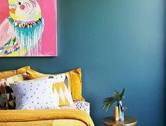 deco bleu canard, couleur mur et linge de lit jaune, couverture multicolore, tableau de peinture, habillage murs, perroquet sur un fond rose, table basse design, coussins multicolores