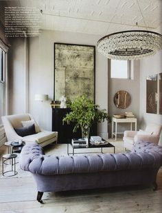 Elegant White Elle Home Interior Decor Idea For Living Room With Luxurious Chandelier, White Wall, Blue Sofa, Black Table With Green Plants,...