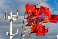 stock photo of red marker flags on fishing boat against cloudy blue sky horizontal