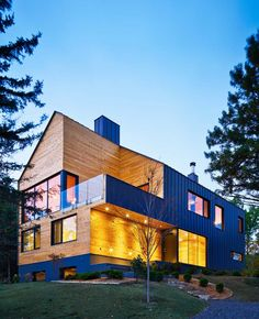 A modern farmhouse in Quebec, Canada.  The exterior combines wood and grey colored concrete.