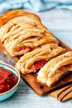 Lecker belegen, hübsch falten, mit Knoblauch-Parmesan-Butter bepinseln und ab in den Ofen – so easy geht unser geflochtener #Blätterteig mit Salami-Mozzarella-Füllung. In fruchtige #Salsa getunkt ist dieser Turbo-Snack ein echtes Highlight auf jeder #Party! #blätterteig #snacks #fingerfood #mozzarella #salami #rezepte #partyfood #rezeptideen #backvideo