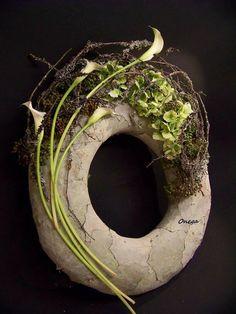 Leaf covered wreath and modern flower arrangement