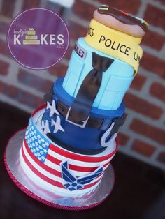 Air Force Cop cake All 3 tiers are iced in buttercream.  Police uniform is based on one of my previous designs.  Belt, handcuffs, shirt pockets, donut, American Flag are marshmallow fondant (MMF).  Police tape is rice cereal covered in MMF.  Air Force Logo is made from Gumpaste.