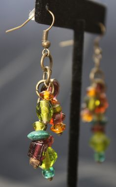 These unique up-cycled earrings were created from the beads of a bracelet found in a local thrift store. A mix of colored glass, plastic and wooden beads of varying sizes and shapes are clustered together on a brass tone chain. They measure approximately 2 and 1/2 from the hole and are finished with new brass tone fish hooks and rubber stoppers. You can find a slight variation on this piece here: https://www.etsy.com/listing/459853536/up-cycled-jewel-toned-bead-c...
