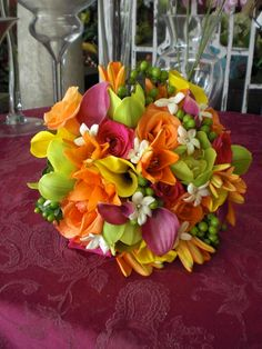 Bridal bouquet of yellow and pink miniature Calla Lilies, orange Asiatic Lilies, orange and hot pink Roses, green Cymbidium Orchids, green Hypericum Berry, and Stephanotis